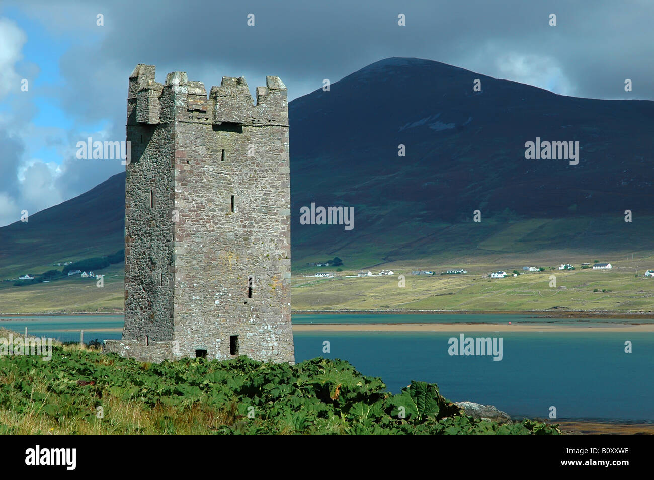 An old castle tower ruin on Achill Island (Ireland) on a sunny day, in the background a large hill on the mainland - Stock Image