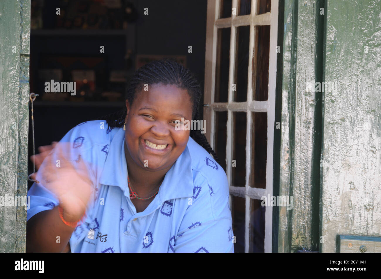 African Woman Laughing and Waving from the Window - Stock Image
