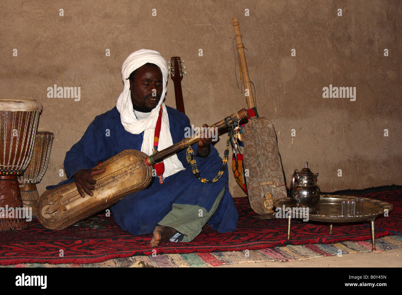 Playing the Hajhouj or guembri, Three stringed percussive lute, used in traditional Gnawa or Gnauoa Music of Khamlia - Stock Image
