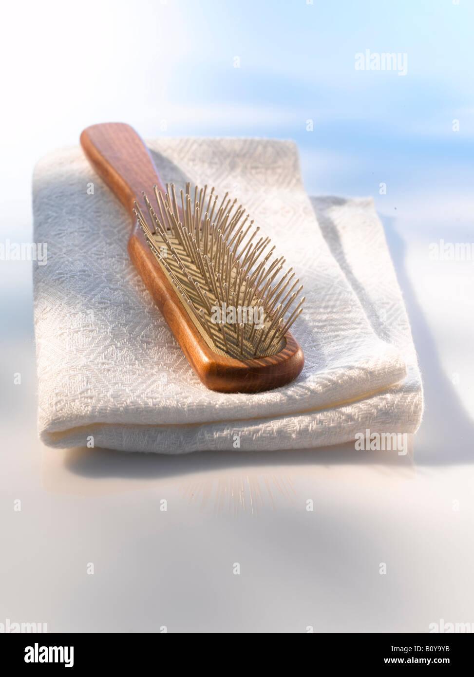 Hairbrush on white towel, close up - Stock Image