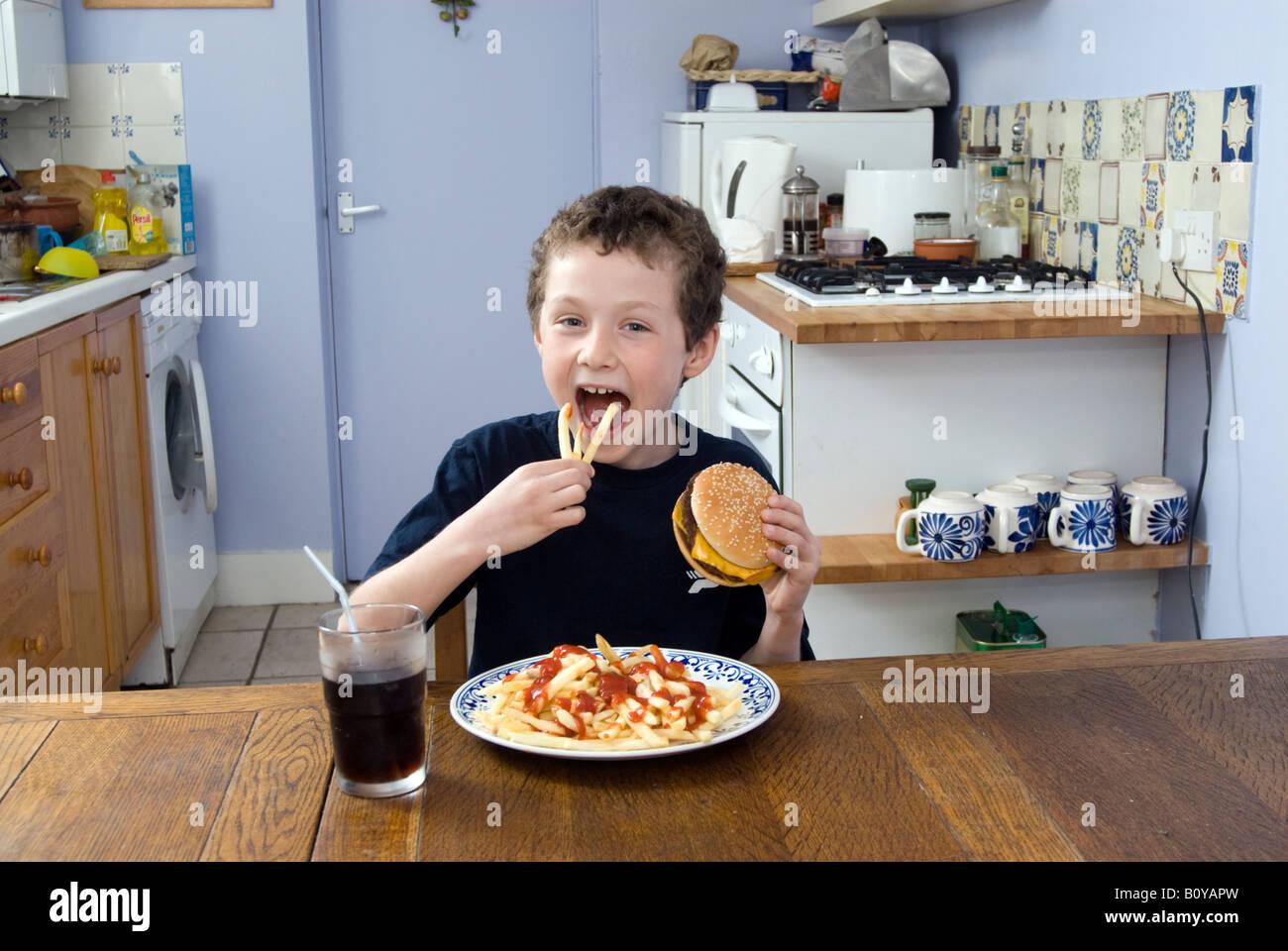Boy eating junk food at home, England UK - Stock Image