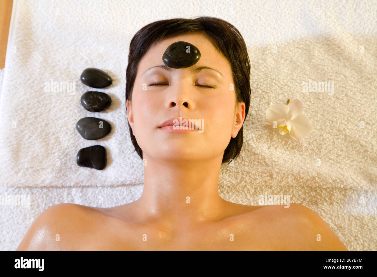 Young woman in spa, receiving lastone therapy - Stock Image
