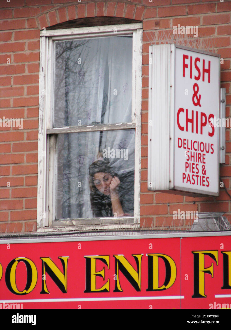 Woman Looking Out Of Window Above An Englisch Snack Bar Fish And