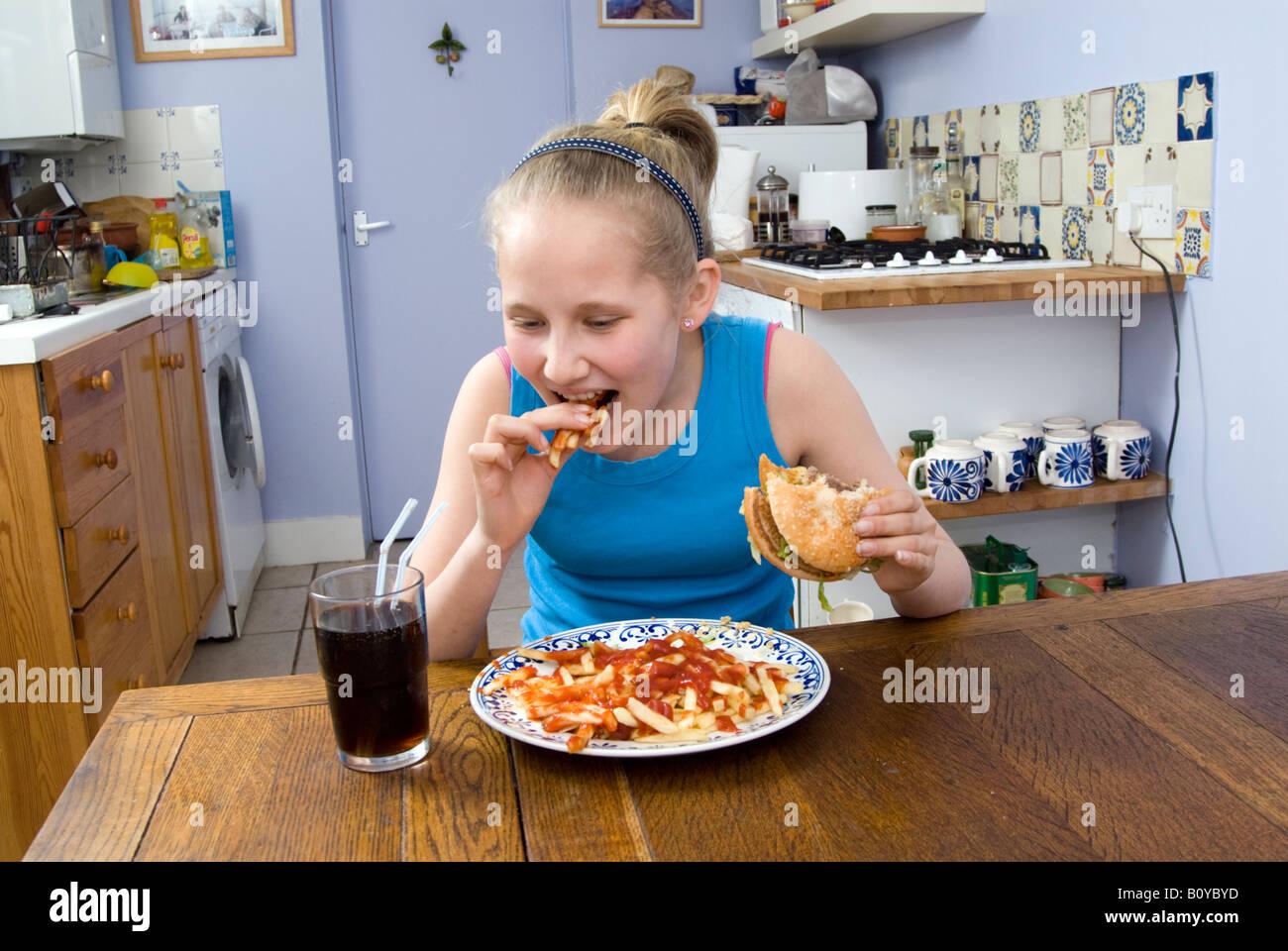 Girl eating junk food, England UK - Stock Image