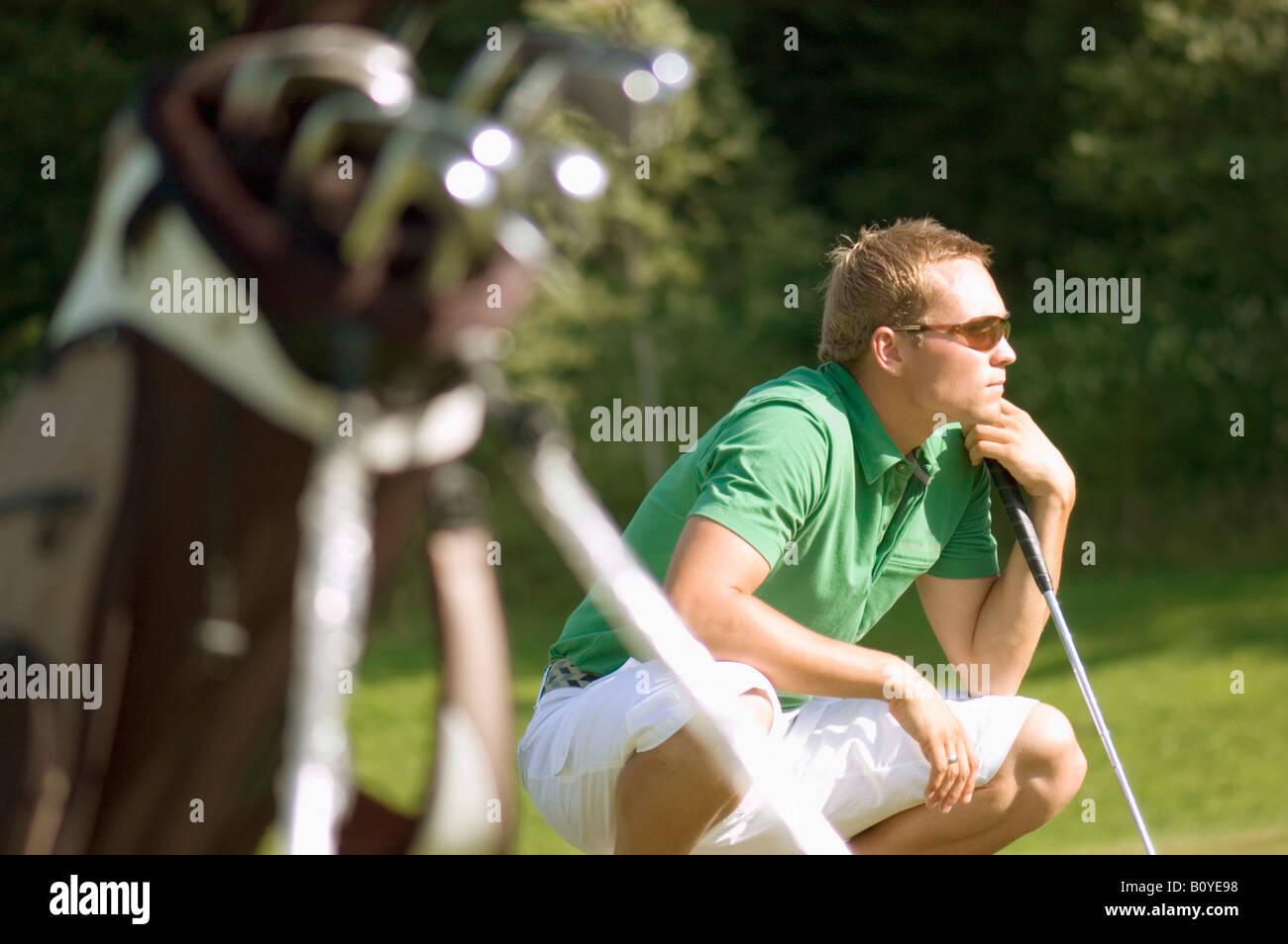 Golf player squatting, musing - Stock Image