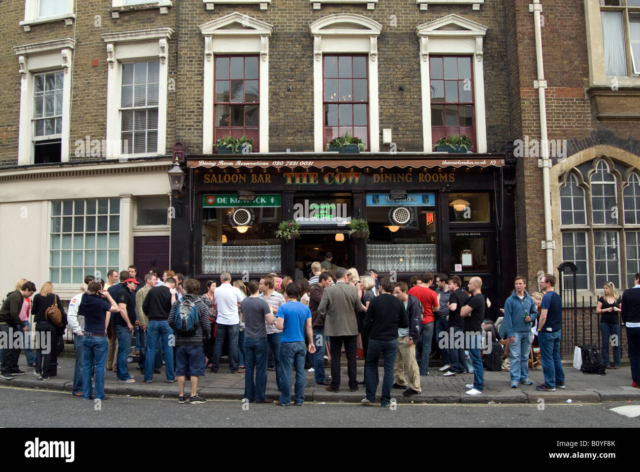 People drinking in the street outside The Cow pub in Westbourne Park Road, Notting Hill, London England UK Stock Photo