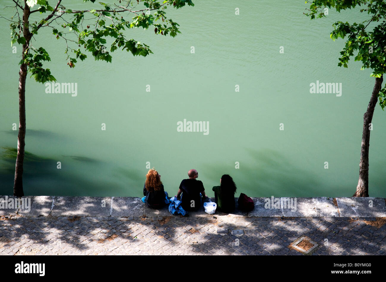 Tourists sitting on the bank of the Tiber river in Rome, Italy - Stock Image