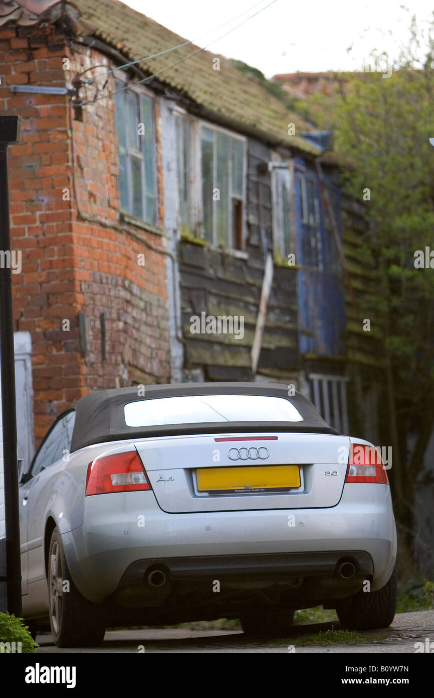 Audi Cabriolet sports car parked outside old derelict cottage Stock Photo