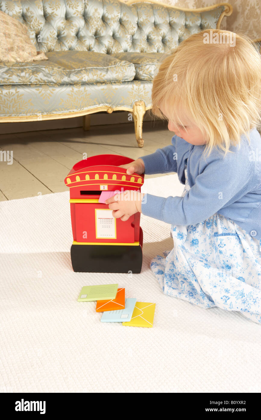 a girl plays with a wooden toy post box posting letters inside - Stock Image