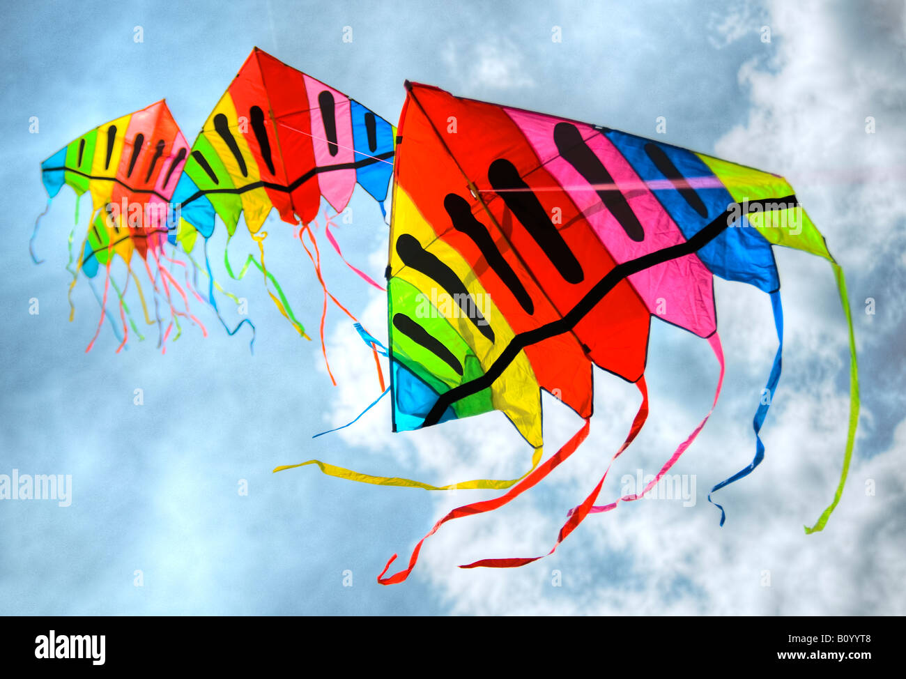 Static line kites flying against a blue and cloudy sky - Stock Image