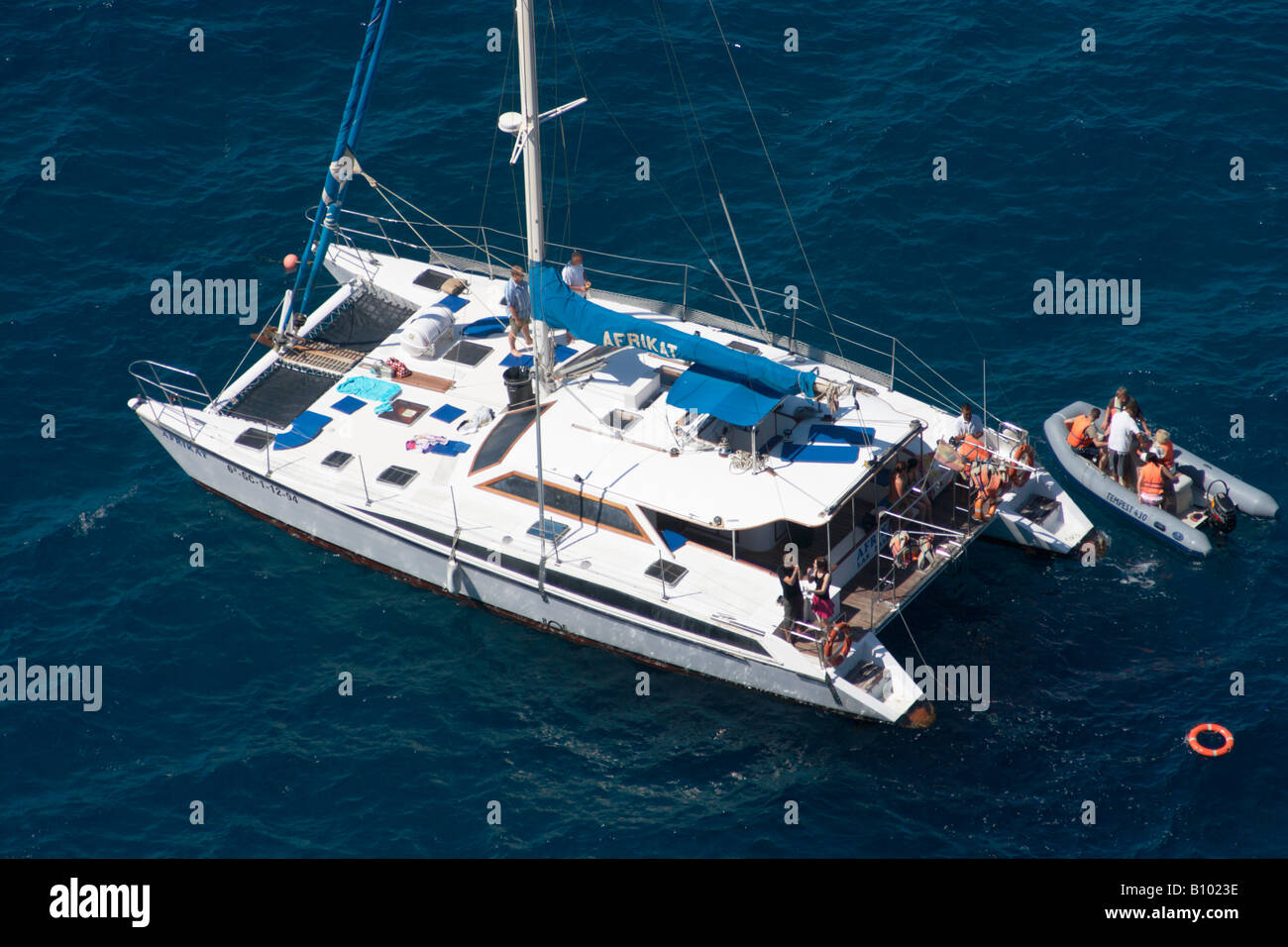 Tourists on catamaran anchored near Puerto de Mogan on Gran Canaria in The canary islands - Stock Image