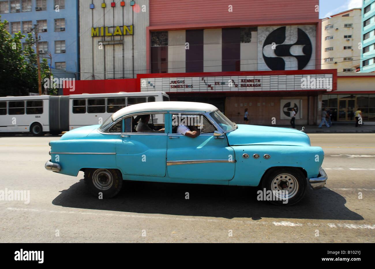Classic American car drives past a cinema in Havana, where 50 year ...