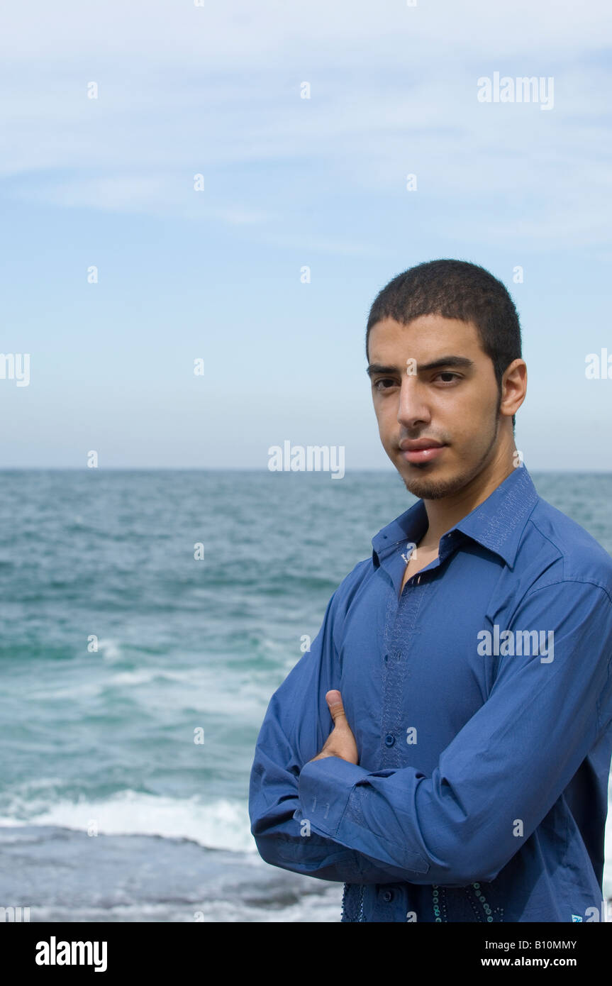 Young ethnic man arms folded by the sea with copy space for text - Stock Image