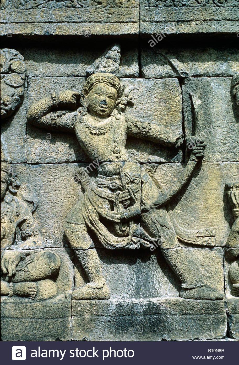 Borobodur Java 850 AD Buddha Shiva with bow and arrow Carving  Copyright A Eaton AAA Collection - Stock Image