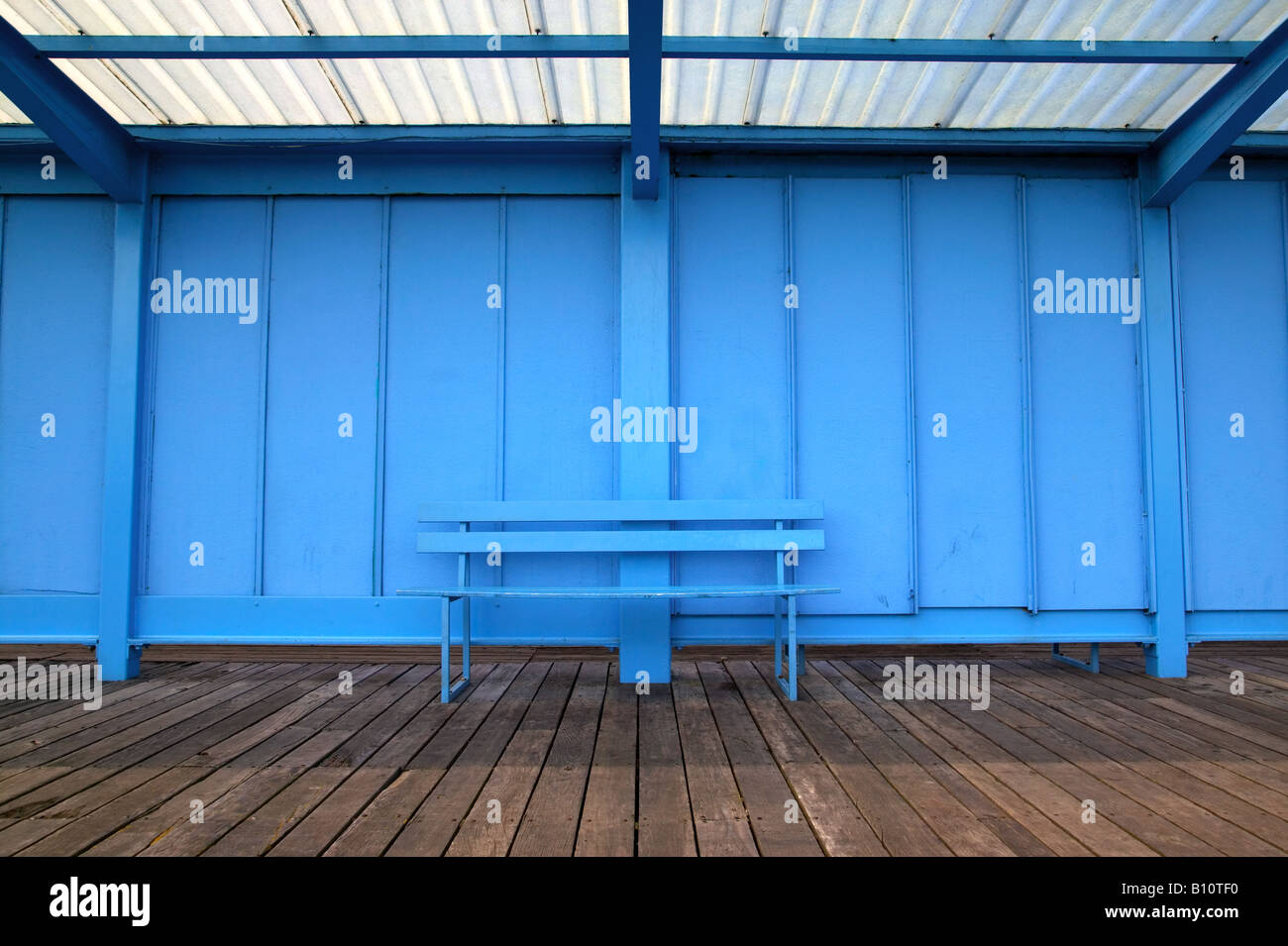 An empty blue bench on an old pier - Stock Image