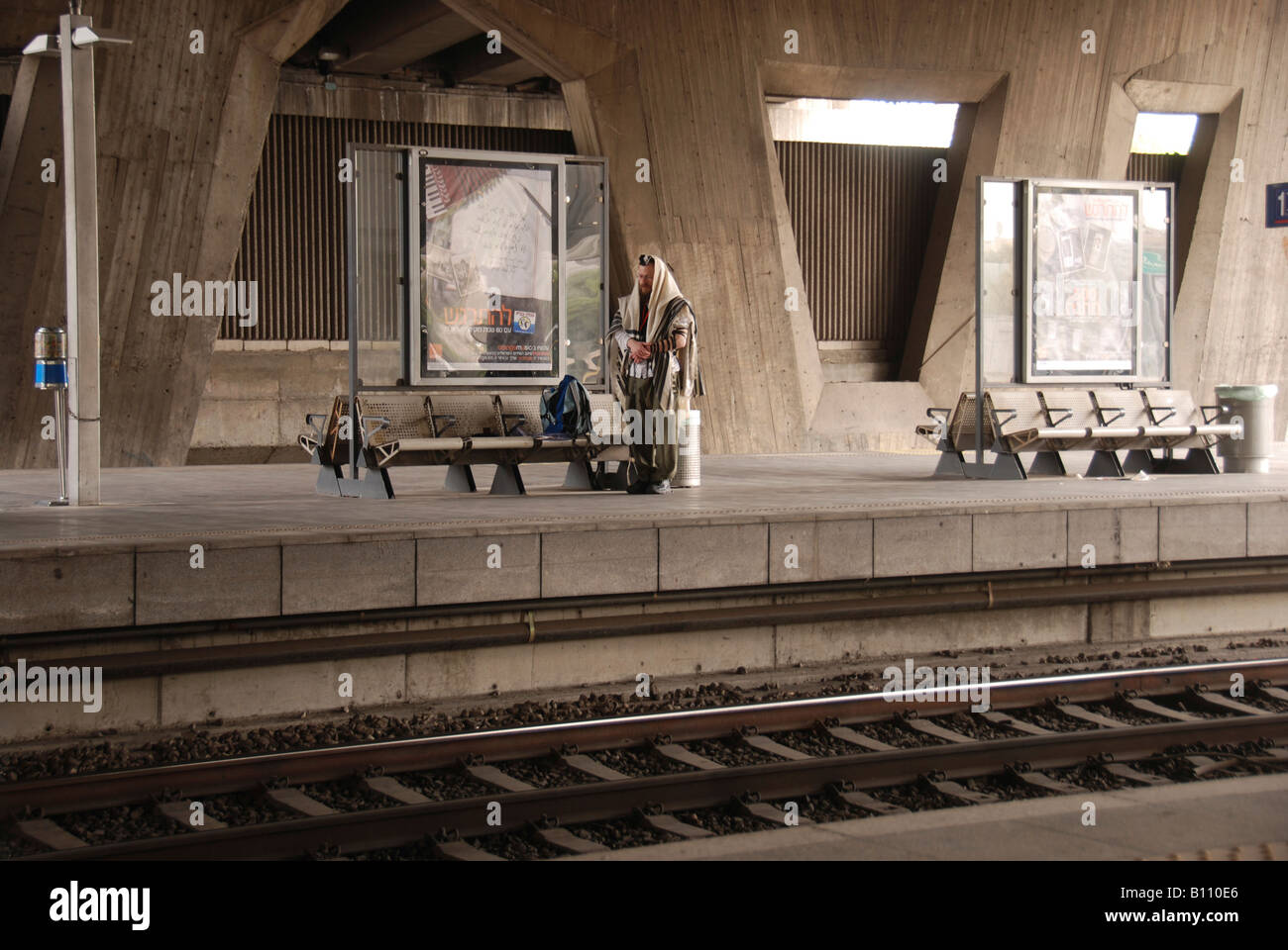 Israel Tel Aviv The interior of the Azrieli Train station Jewish man wrapped in a tallith praying - Stock Image