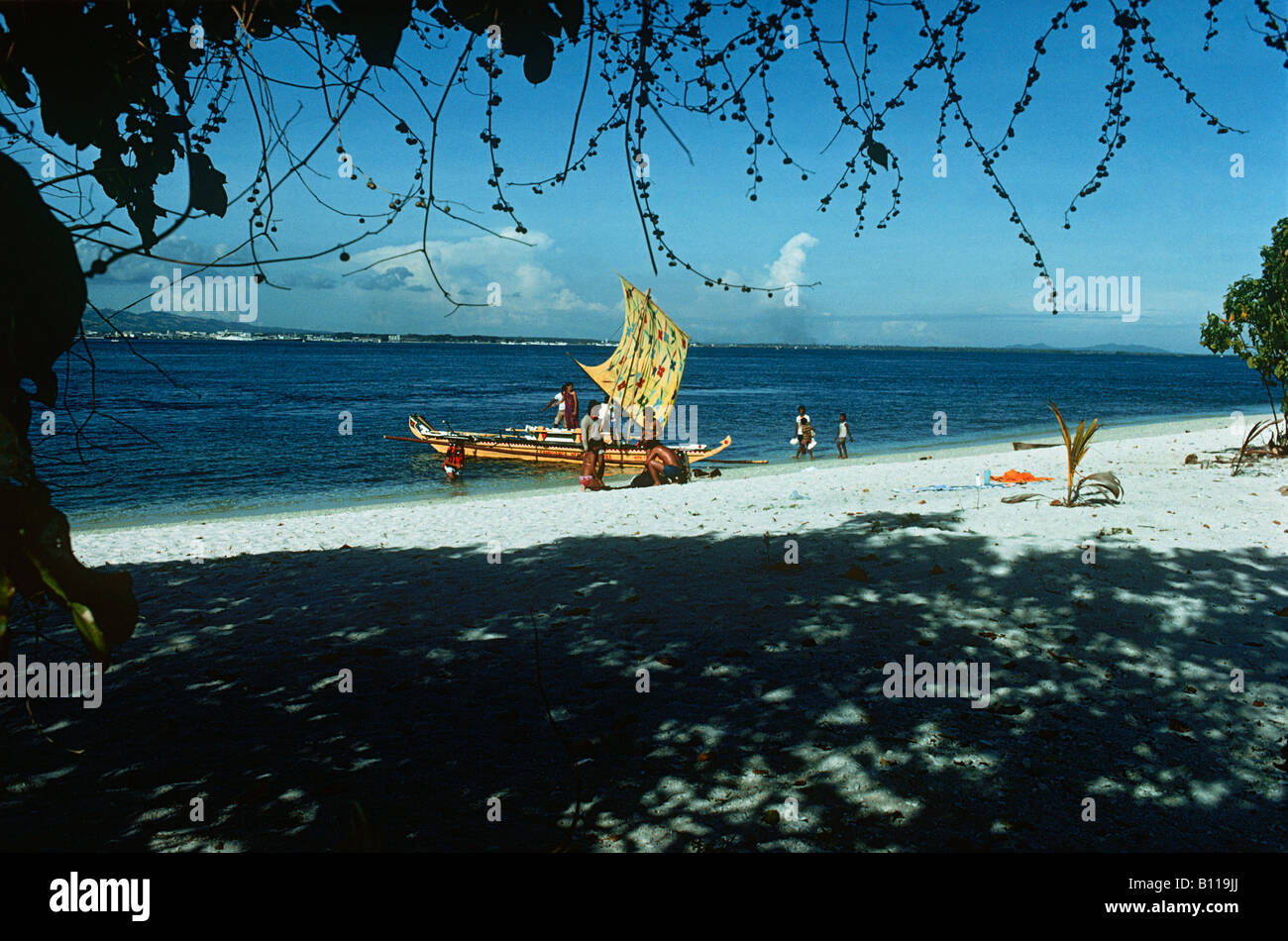 The Philippines. A boat with a bright yellow Vinta (sail) and a group of divers sets sail from a beach on Santa - Stock Image