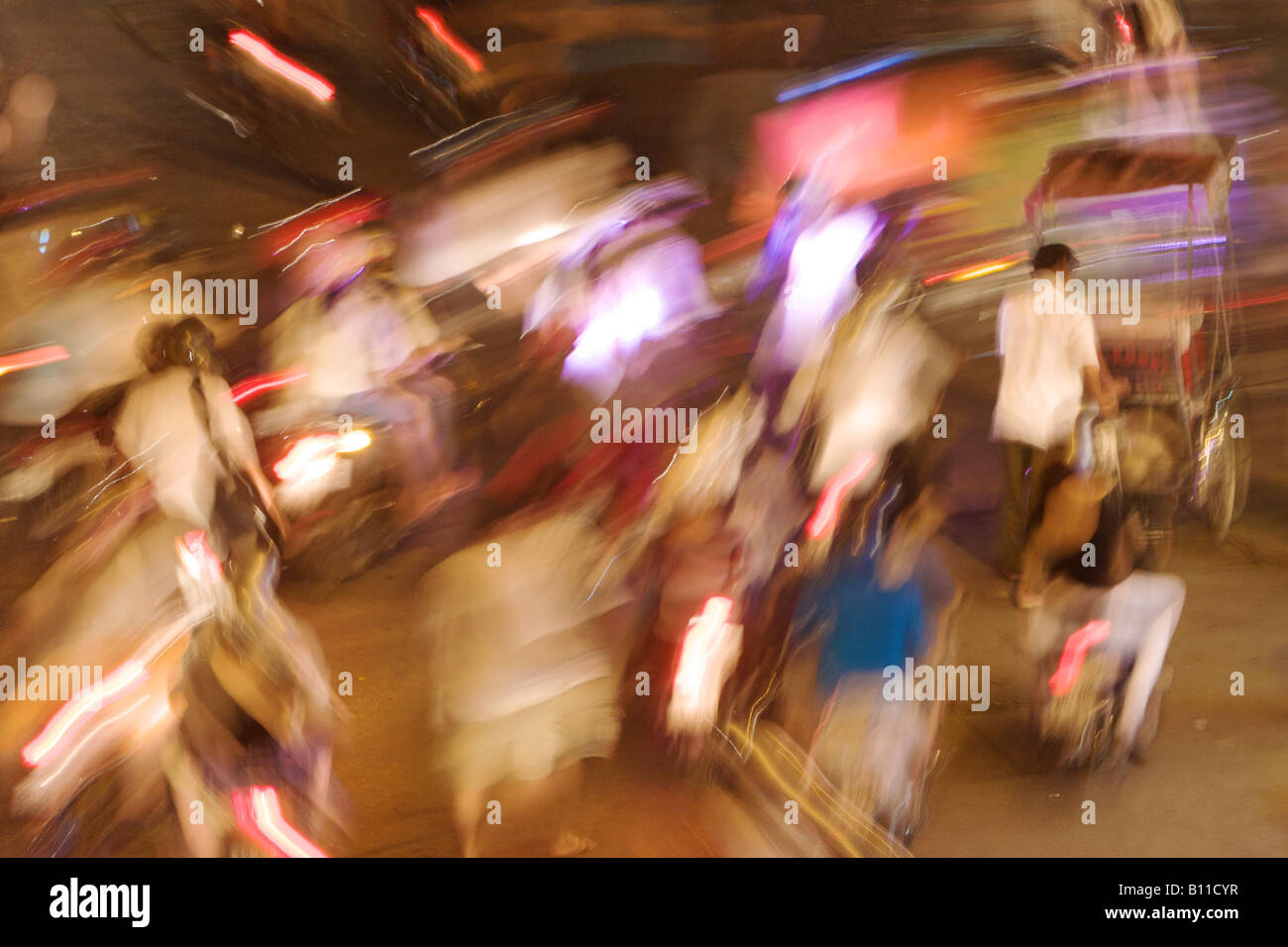 Busy street intersection in Hanoi, Vietnam. Shot from an elevated perspective, at night, with a long exposure and - Stock Image