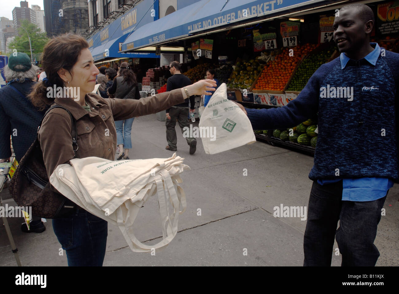Volunteers in front of Fairway Supermarket in New York give away reusable canvas bags to shoppers to replace the - Stock Image