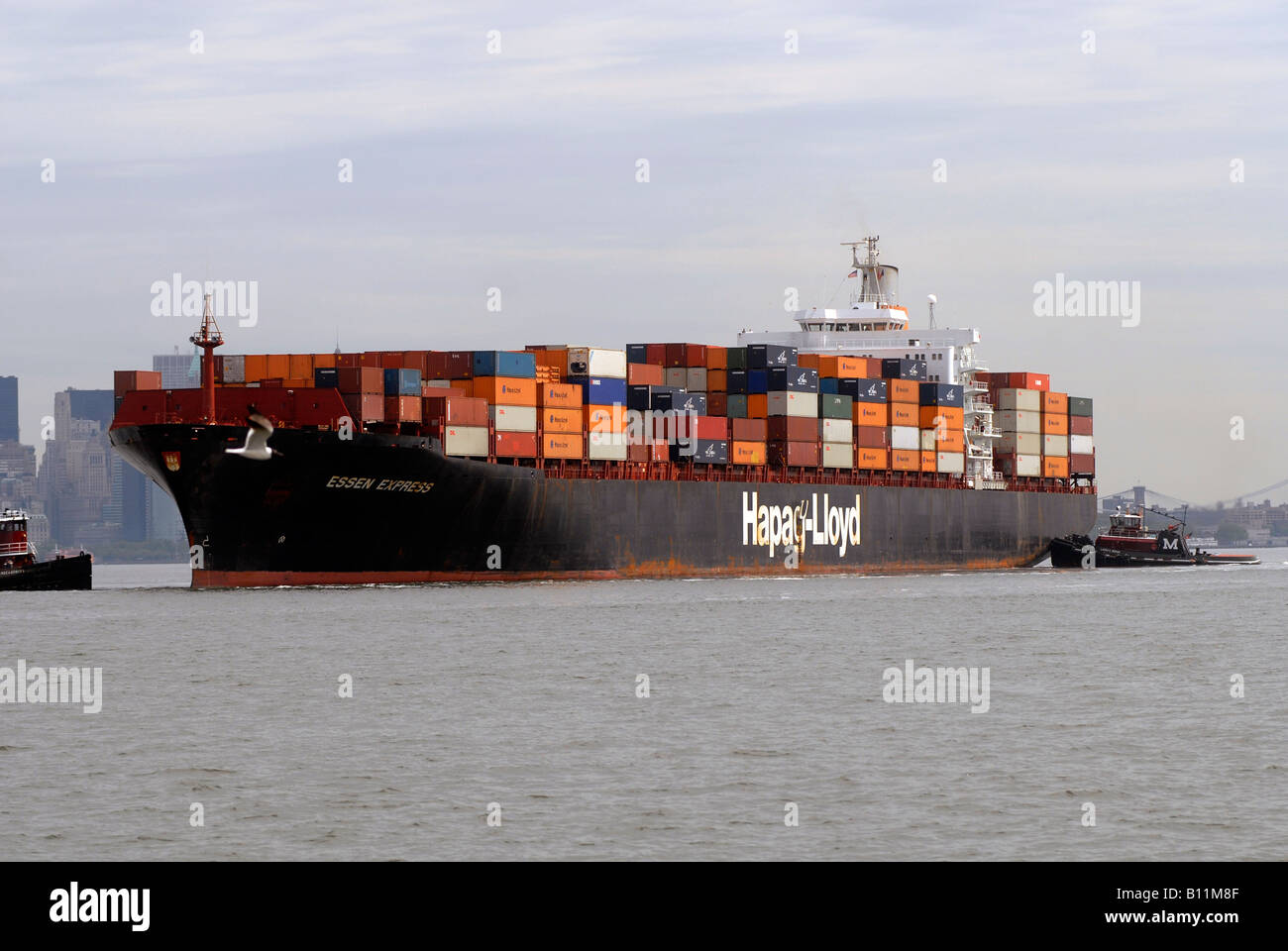 The Essen Express of the Hapag Lloyd line leaves port on the Hudson River North River in New Jersey laden with containers - Stock Image