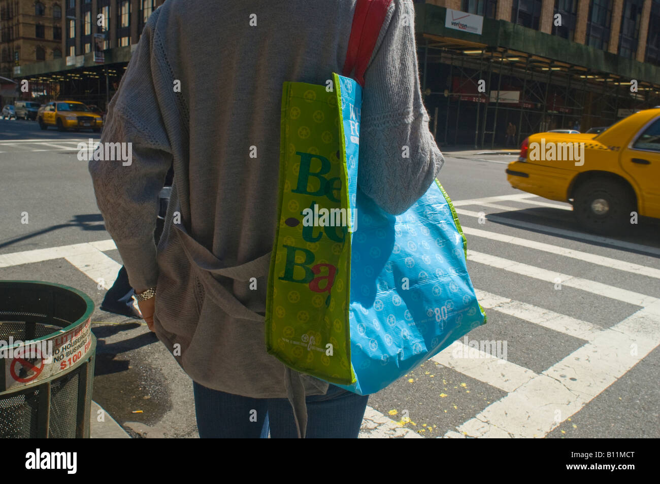A woman outside of Whole Foods Supermarket in the New York neighborhood of Chelsea with a reusable shopping bag - Stock Image
