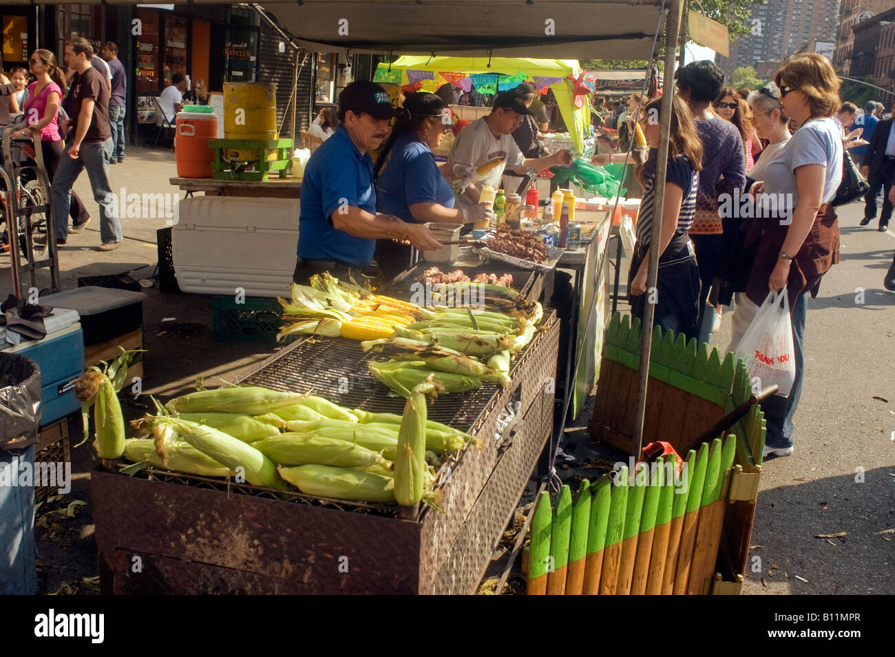 Corn is grilled at the famous Ninth Avenue Food Festival in New York - Stock Image