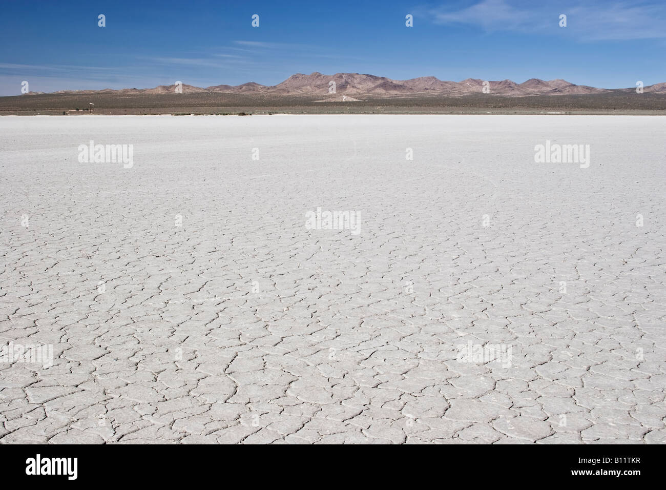 El mirage Dry lake bed with mountains in the distance and a clear blue sky. Stock Photo