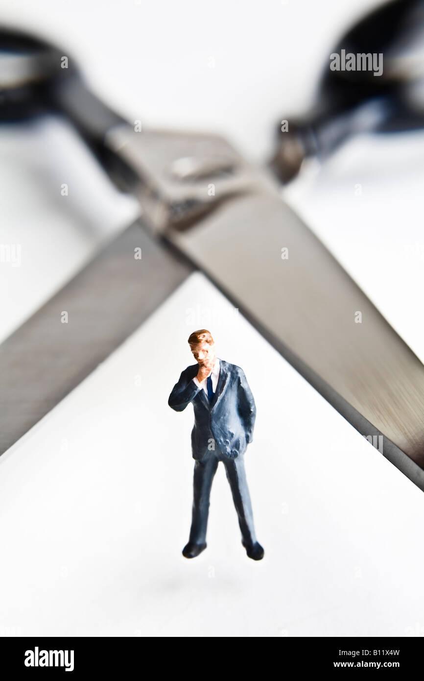 Businessman figurines standing next to scissors - Stock Image