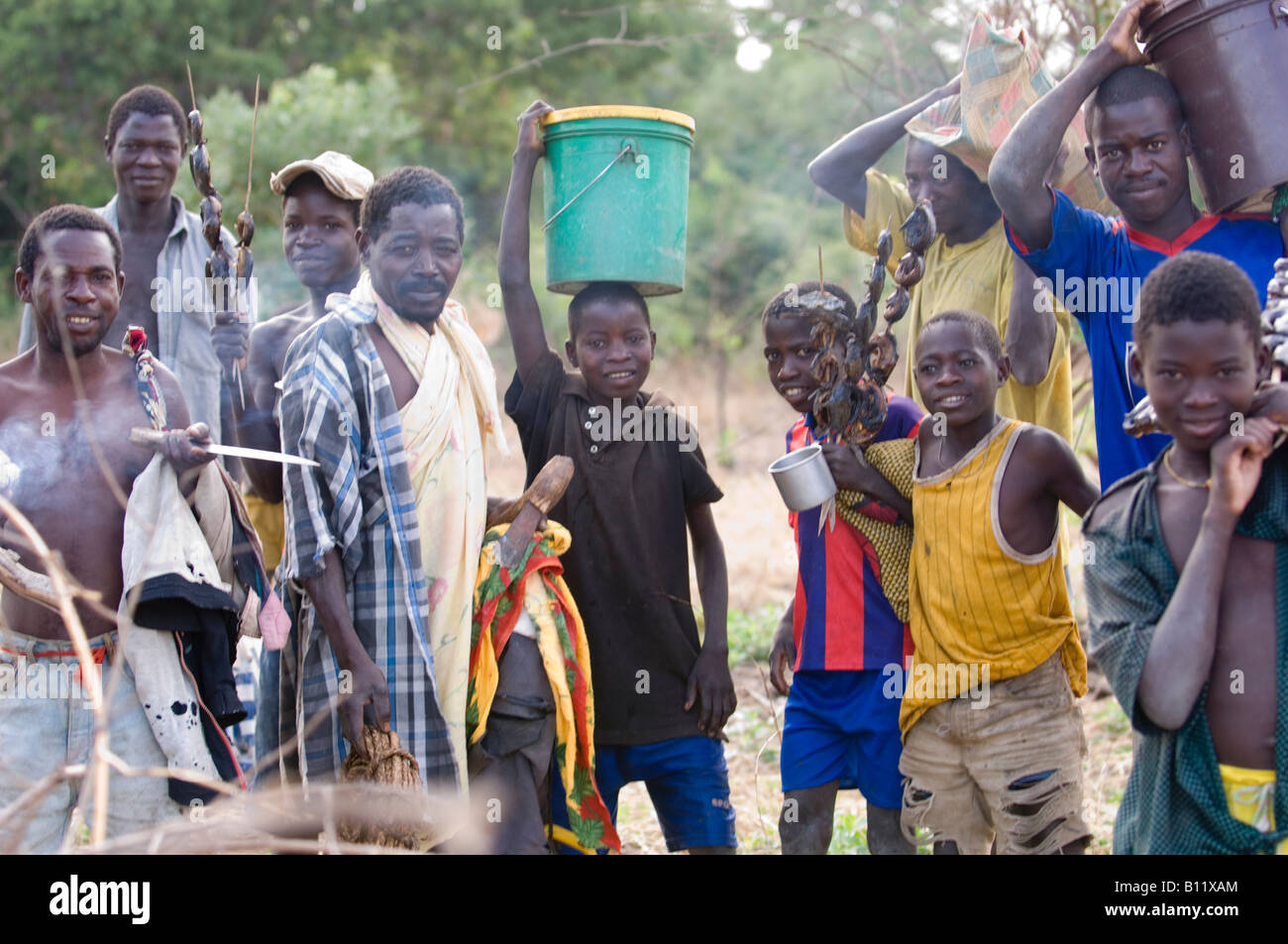 Group of people hunting for nutritious food in Niassa Reserve ( Mozambique ) collect catfish on a skewer. - Stock Image