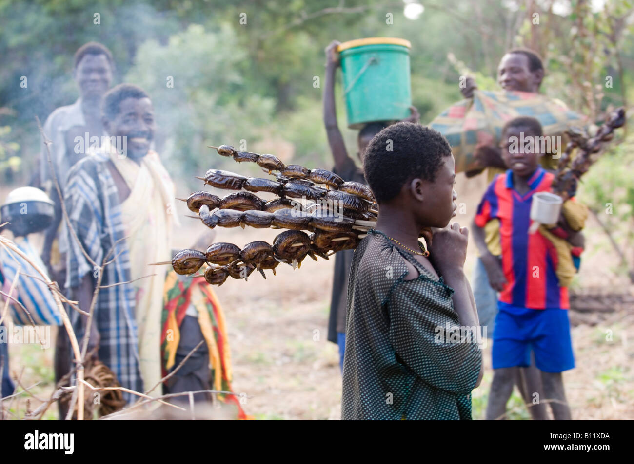Group of people hunting for food in Niassa Reserve ( Mozambique ) collect catfish on a skewer. - Stock Image