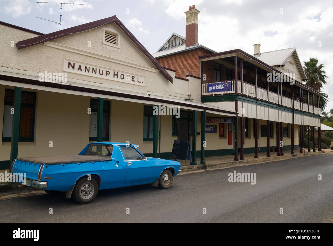 An old blue Holden utility parked outside a traditional country town pub, Nannup, Western Australia - Stock Image