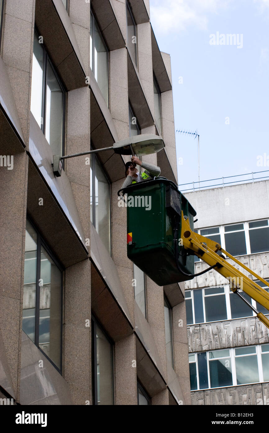 man fixing street light streetlight using cherrypicker cherry picker - Stock Image