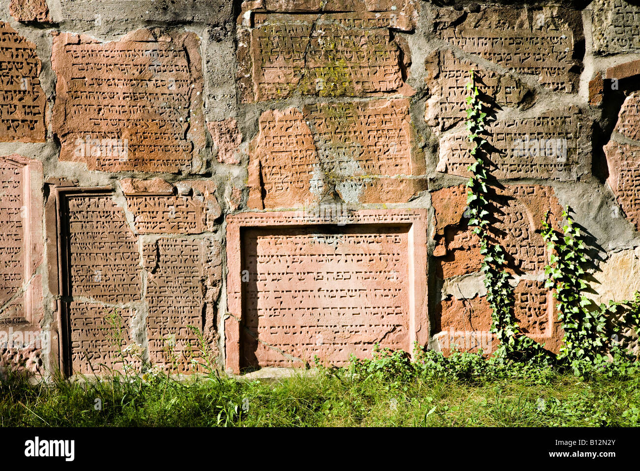 Memorial wall with Hebrew writing in Jewish cemetery the Alter Judenfriedhof or Herliger Sand Worms Germany - Stock Image