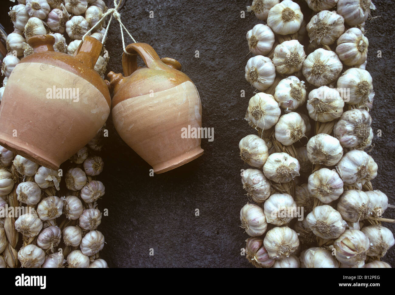 strings of fresh garlic and a couple of clay water jugs hanging on a wall outside a small Spanish shop - Stock Image
