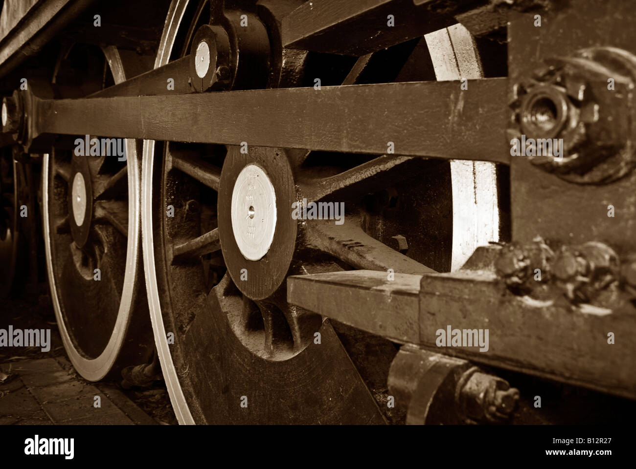 great steam train locomotive wheels closeup image in rich sepia - Stock Image