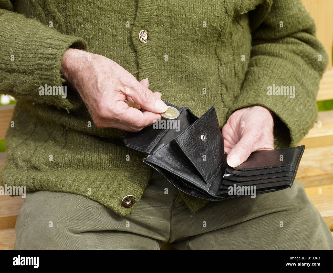 old hands of a senior counting less money in a purse - Stock Image
