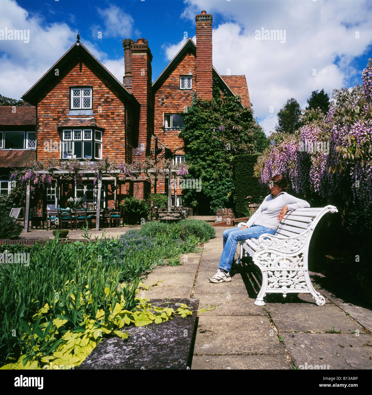 Woman relaxing in a garden Marle Place Brenchley Nr Tonbridge Kent England UK. - Stock Image