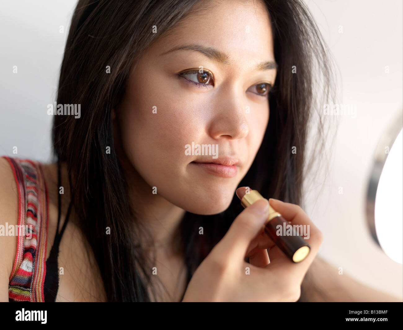 Young Asian women applying lipstick. - Stock Image