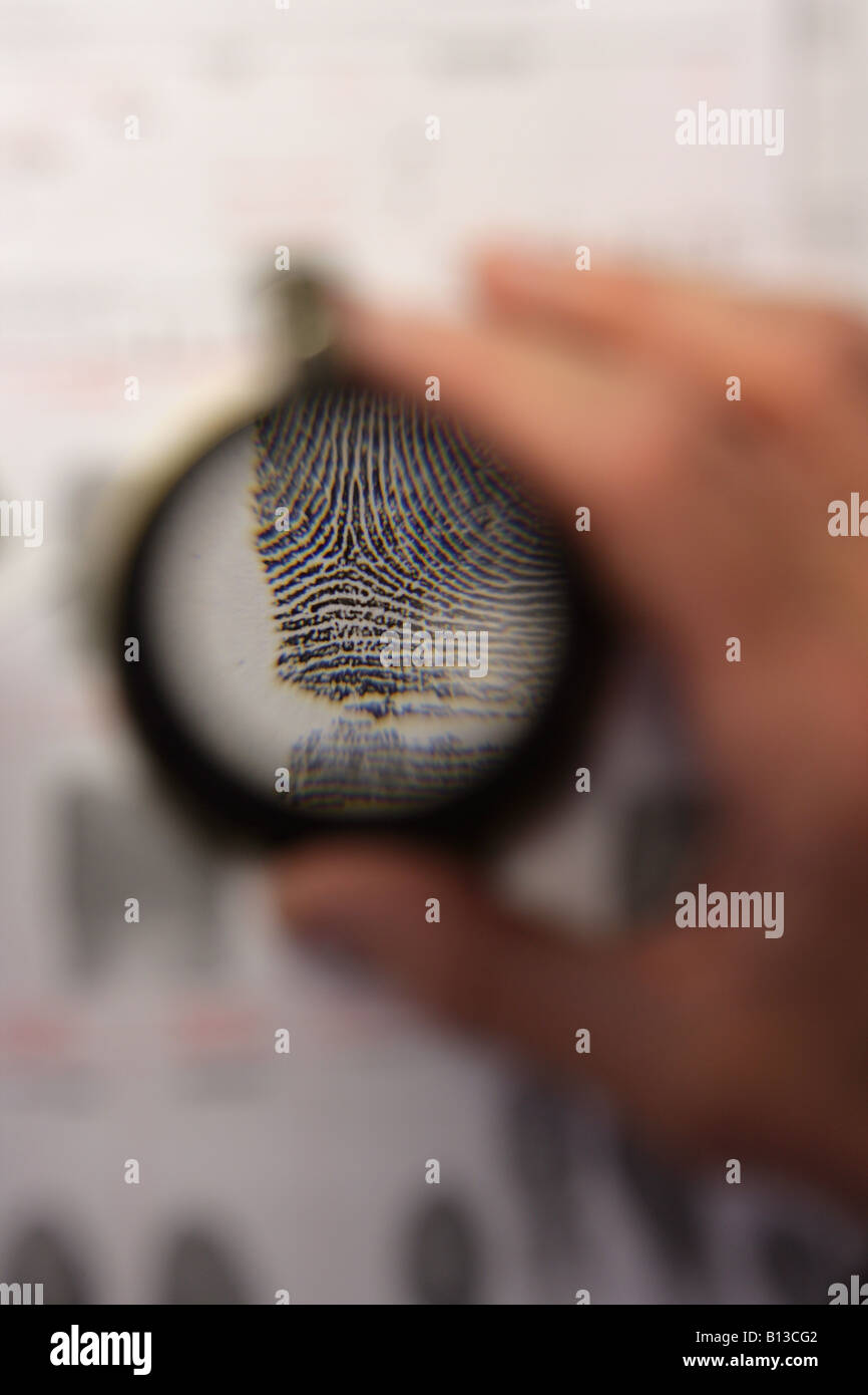 Close up of a person inspecting a sheet of fingerprints using a magnifying glass - Stock Image
