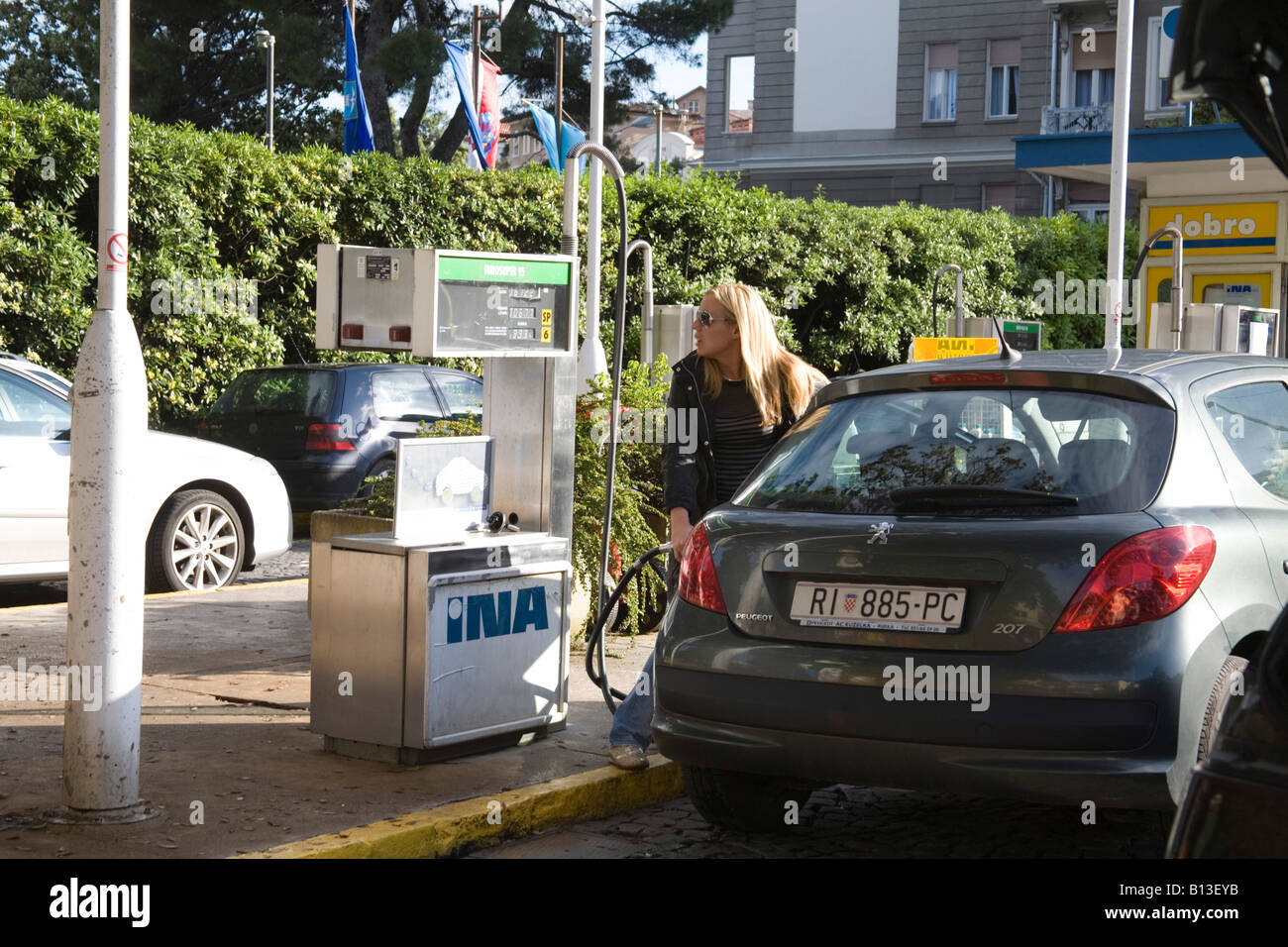 Croatia Europe May Blonde haired woman in a petrol station filling up her car with fuel - Stock Image