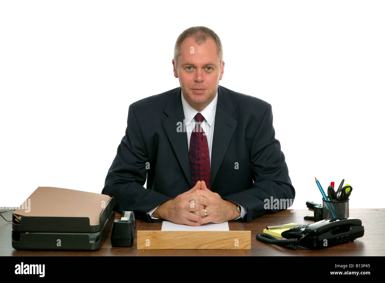 Portrait of a businessman sat at his desk against a white background - Stock Image