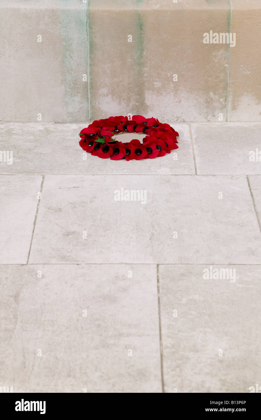 A single poppy wreath at the base of a war memorial on rememberance Sunday - Stock Image