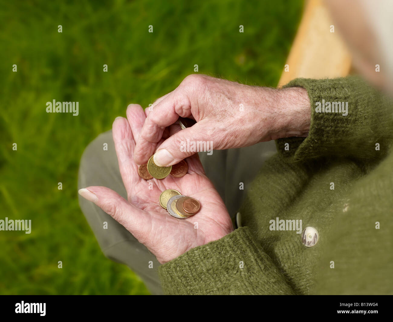 old hands of a senior counting less money, coins - Stock Image