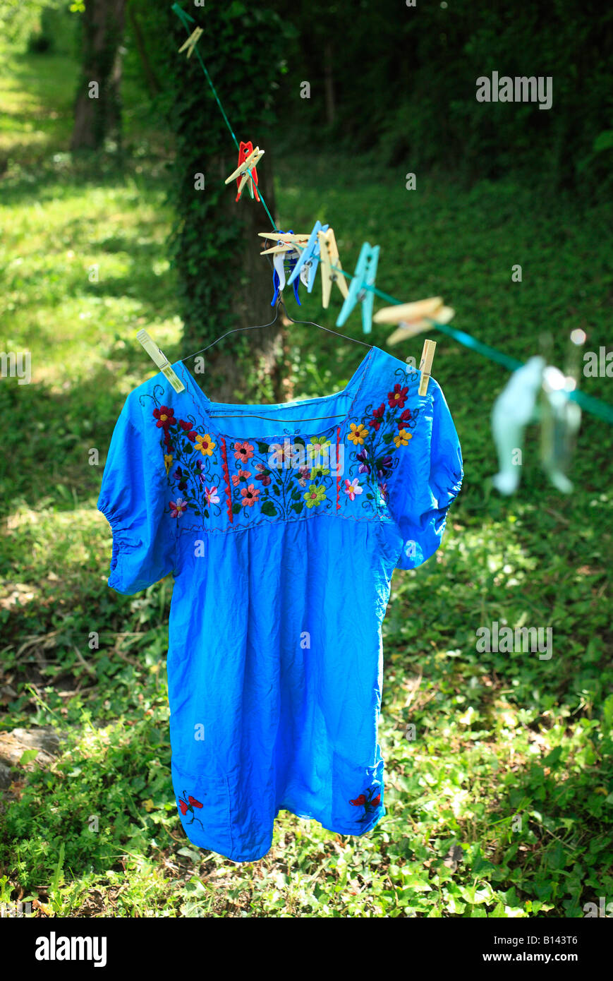 A blue blouse with flowers hanging on a clothesline in a green garden under trees in Le Thor, Provence, France - Stock Image