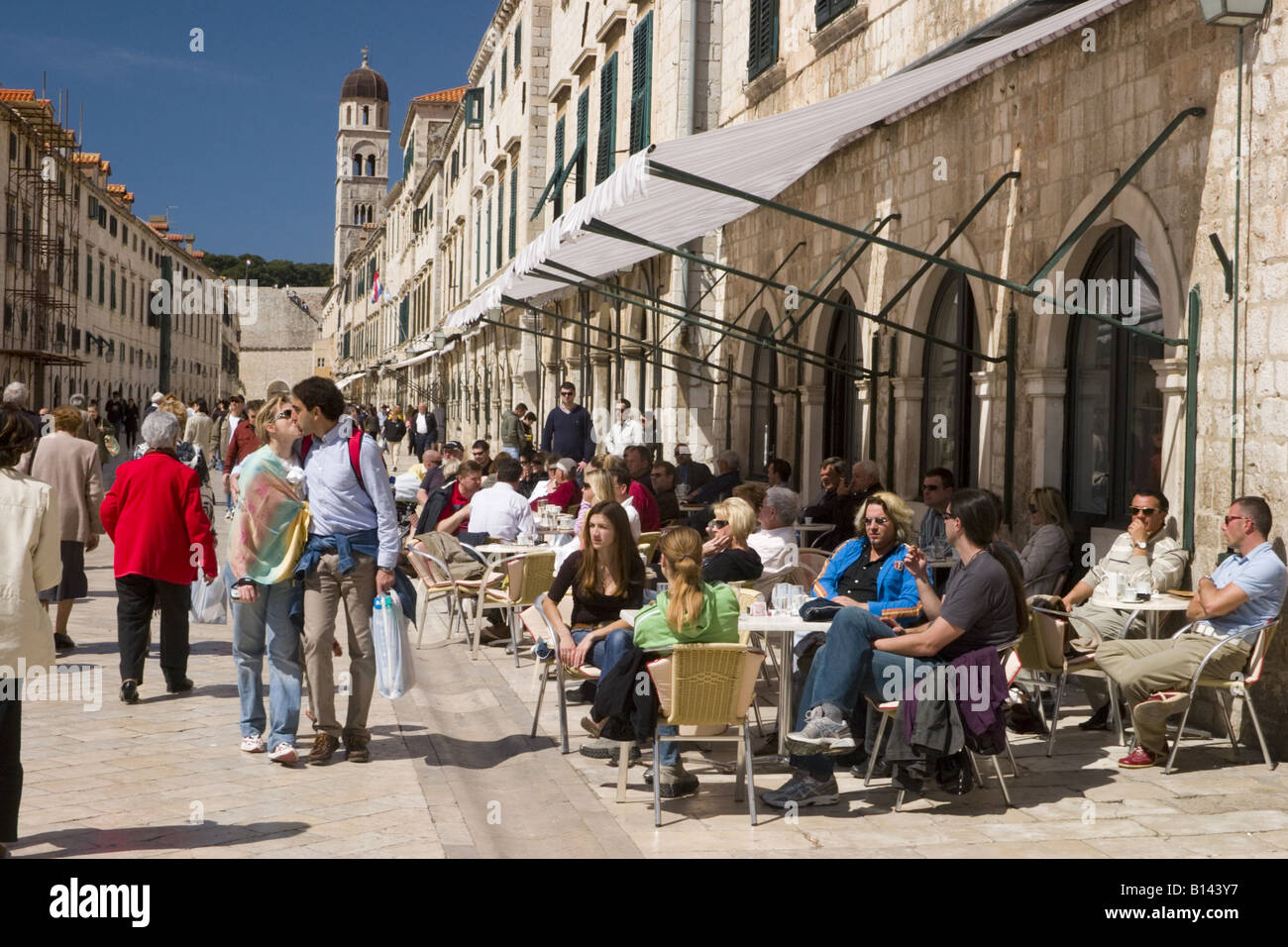 Customers at cafe with couple kissing on Stradun the main street of Dubrovnik old city Croatia - Stock Image