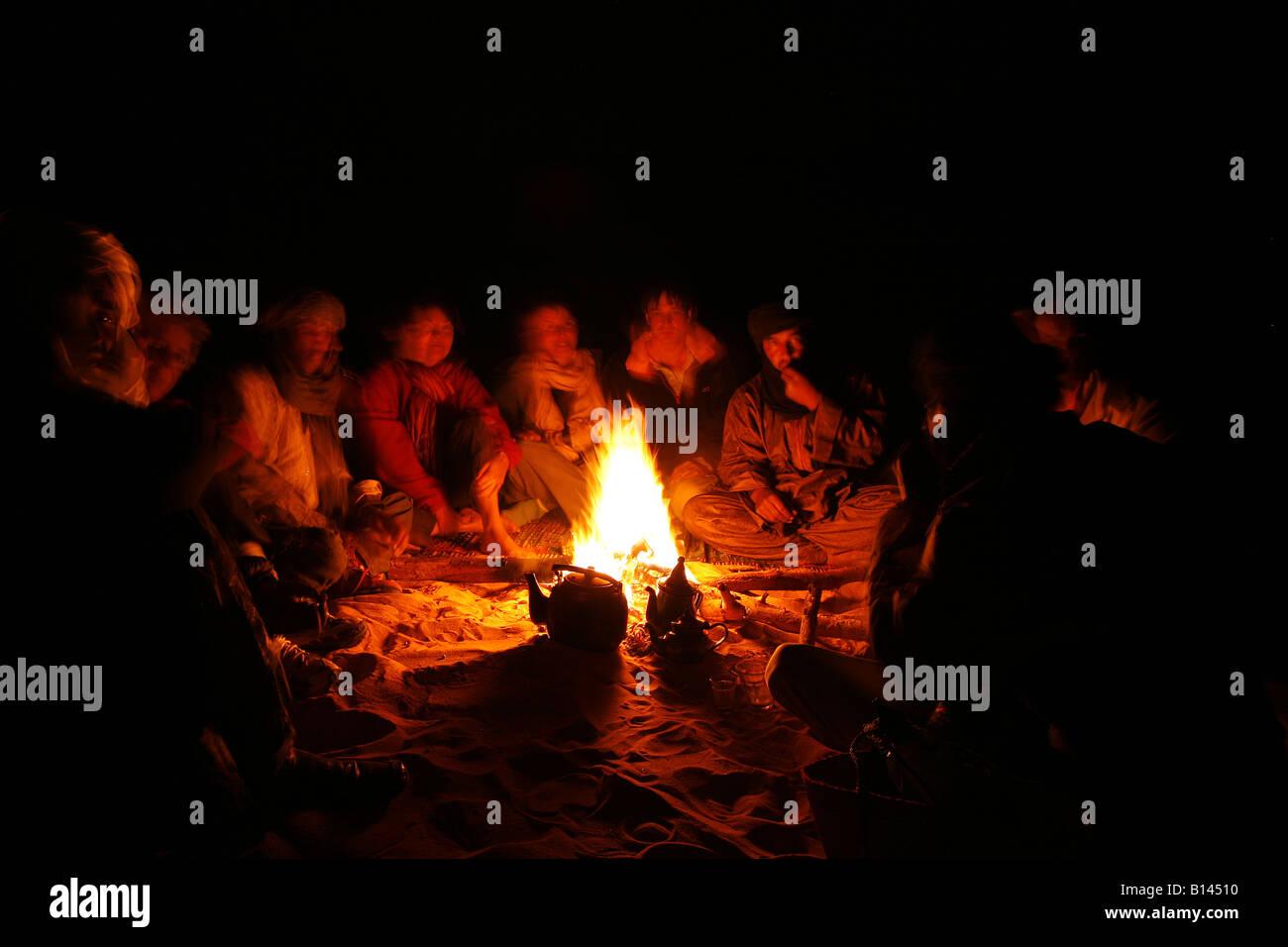 Tuaregs and tourist in Campfire night Oued Tin Tarabine Tassili Ahaggar Sahara desert Algeria - Stock Image