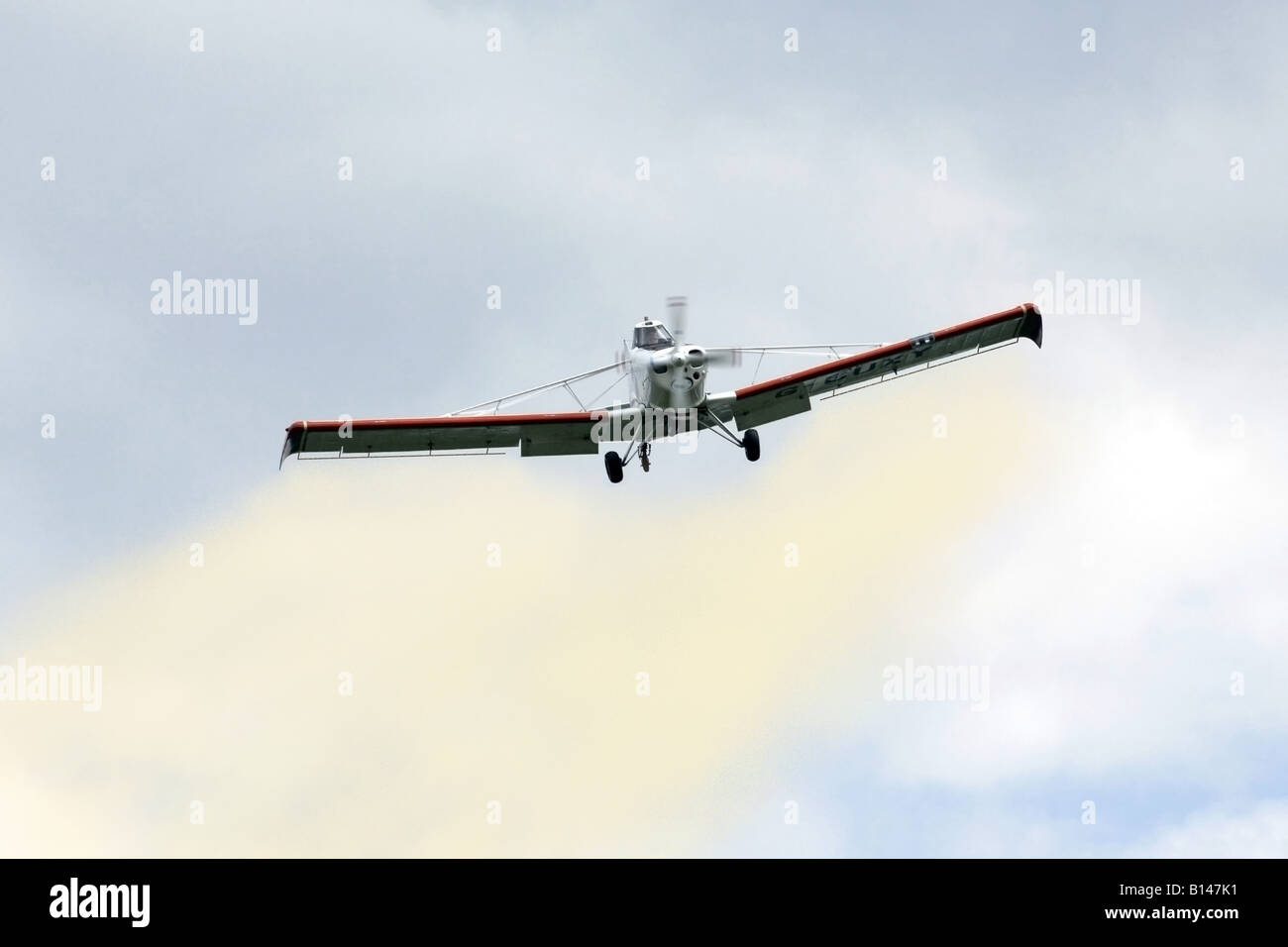 Crop duster aircraft spraying a cocktail of chemicals onto crops in the field below - Stock Image