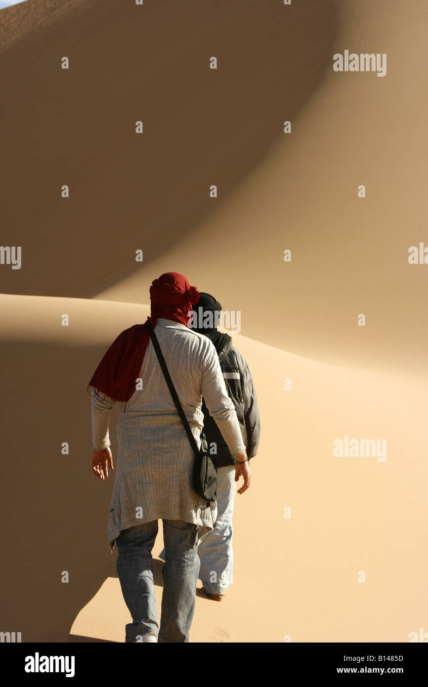 Tourist following tuareg in Oued Tin Tarabine Tassili Ahaggar Sahara desert Algeria - Stock Image