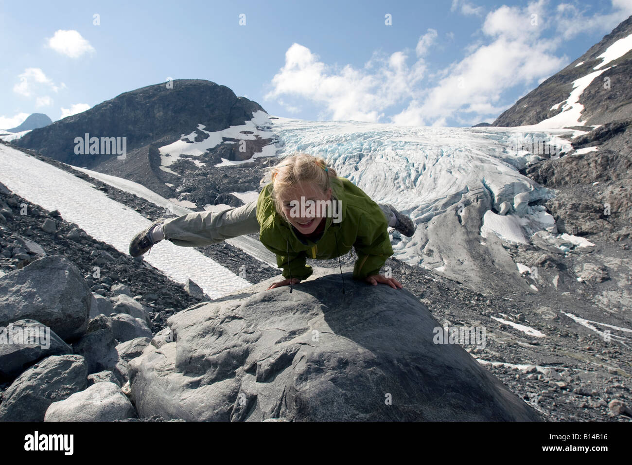 Eight year old blond girl performing acrobatic gymnastics in front of glacier at Jotunheimen in Norway Stock Photo