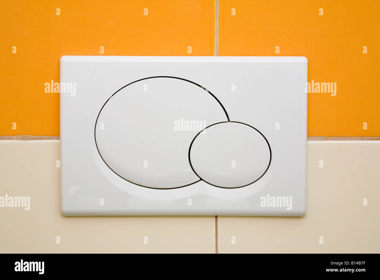 Dual toilet flush with dual economy flush button on tiled wall in public convenience WC - Stock Image
